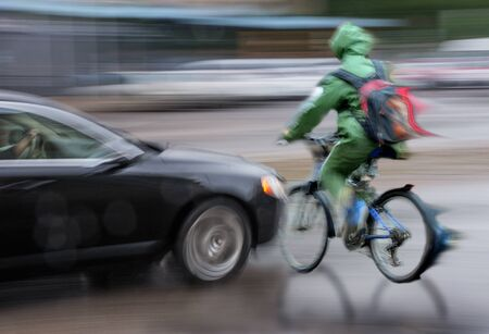 Photo pour Dangerous city traffic situation with cyclist and car in the city in motion blur. Defocused image - image libre de droit