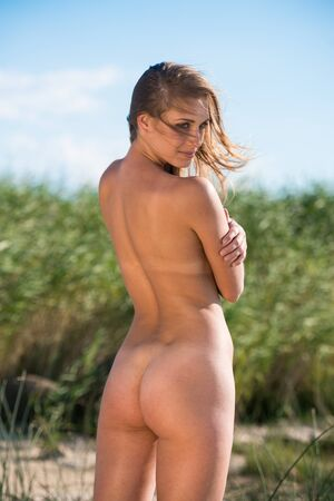 Photo pour Young nude woman posing on nature background. Sexy blonde enjoying summer time - image libre de droit