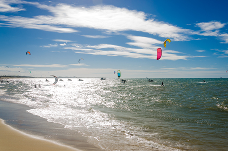 The sunset with kite surfers enjoying the sea at evening