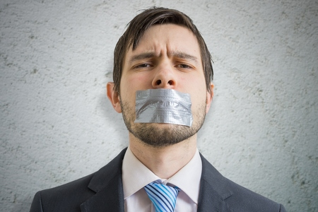 Censorship concept. Young man is silenced with duct tape over his mouth.