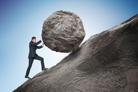 Photo pour Sisyphus metaphore. Young businessman pushing heavy stone boulder up on hill. - image libre de droit