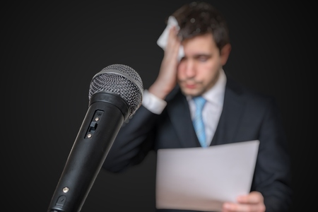 Photo pour Microphone in front of a nervous man who is afraid of public speech and sweating. - image libre de droit