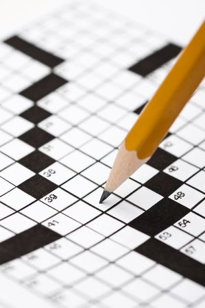 Vertical close up of a sharp pencil on a crossword puzzle