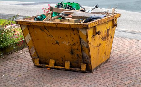 Foto de A yellow skip full of rubbish ready to be collection - Imagen libre de derechos