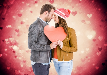 Composite image of romantic couple holding a heart