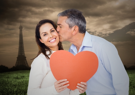 Composite image of romantic couple holding heart with eiffel tower in background