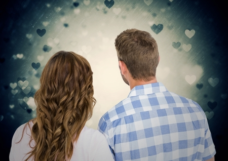 Rearview of romantic couple against digitally generated heart background