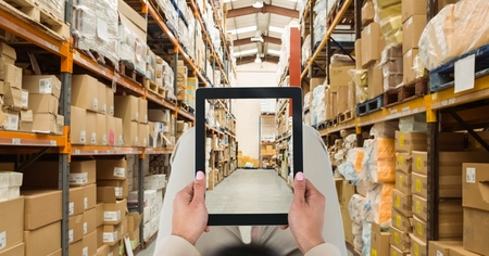 Digital composite of Person photographing warehouse through tablet PC