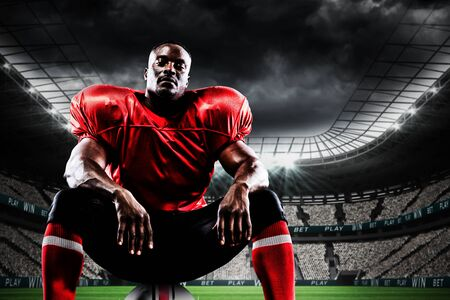 Photo pour American football player against soccer stadium under cloudy sky - image libre de droit