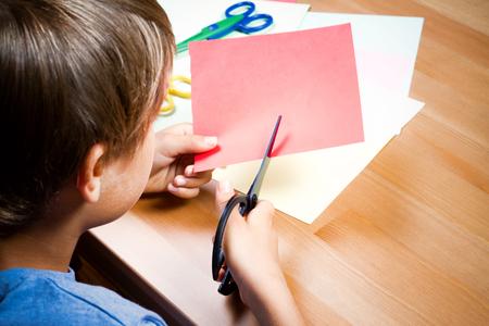 Foto de Child cutting colored paper with scissors at the table - Imagen libre de derechos