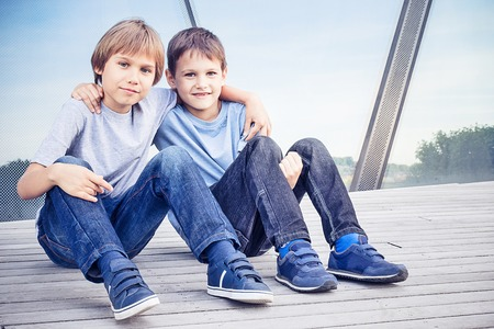 Photo for Two happy kids sitting together and embracing - Royalty Free Image