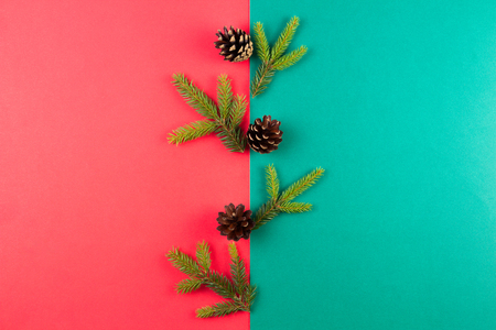 Christmas composition. Fir tree branches and pine cones arranged on red and green background. Top view, flat lay.