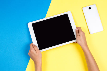 Photo for Kid hands holding tablet computer on blue and yellow background - Royalty Free Image