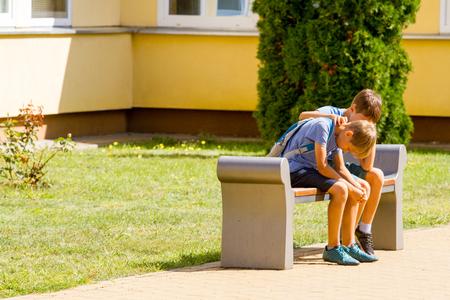 Photo pour Kid comforting consoling upset sad boy in school yard - image libre de droit