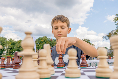 Foto de Kid playing chess at chessboard outdoors. Boy thinking hard on chess combinations - Imagen libre de derechos