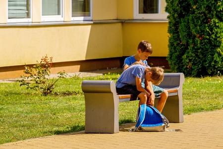 Foto de Kid comforting consoling upset sad boy in school yard - Imagen libre de derechos