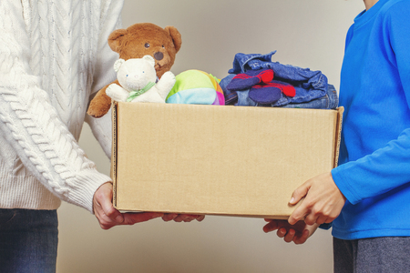 Photo for Donation concept. Donate box with clothes, books and toys in family members hand - Royalty Free Image