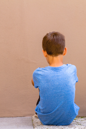 Photo pour Sad alone boy sitting on the ground behind the wall outdoor - image libre de droit