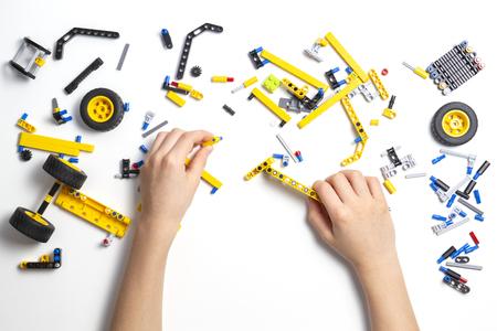 Photo pour Child hands making robot car. Robotic, learning, technology, stem education for children background - image libre de droit