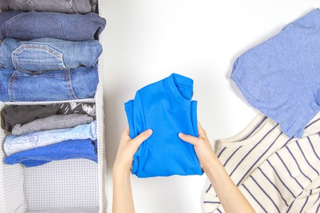 Photo pour Vertical storage of clothing, tidying up, room cleaning concept. Hands tidying up and sorting kids clothes in basket. - image libre de droit