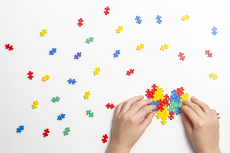 Photo for Child hands making multicolored heart on white background. Top view - Royalty Free Image