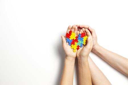Photo pour Hands holding colorful heart on white background. World autism awareness day concept - image libre de droit