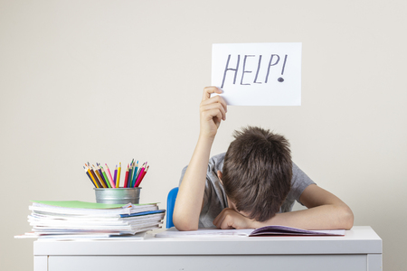 Foto de Sad tired frustrated boy sitting at the table with many books and holding paper with word Help. Learning difficulties, education concept. - Imagen libre de derechos