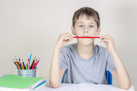 Photo pour Kid doing homework at the table and thinking or dreaming - image libre de droit