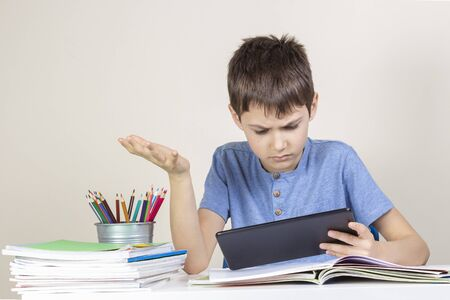 Photo pour Confused,surprised child with tablet computer sitting at table with books notebooks - image libre de droit