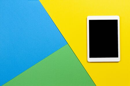 Photo pour Digital tablet computer on light blue, green and yellow background. Top view - image libre de droit