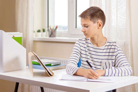 Photo pour Kid with digital tablet computer writing, doing homework at white desk. Online learning, remote education, distance lessons at home - image libre de droit