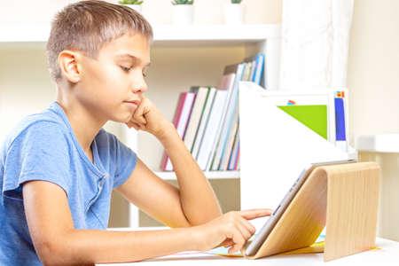 Photo pour Teenage boy with digital tablet computer doing homework. Online learning, remote education, distance lessons, entertainment at home - image libre de droit