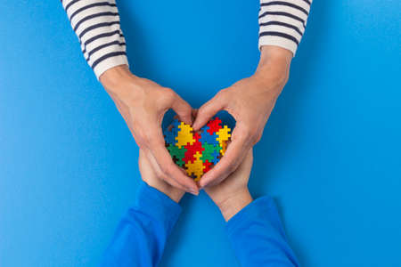 Photo pour World autism awareness day concept. Female and child hands holding puzzle heart on light blue background - image libre de droit