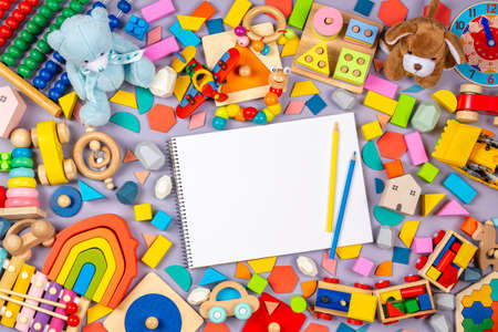 Photo pour Colorful educational wooden plastic and fluffy baby kids toys and blank notebook with colored pencils on gray background. Top view - image libre de droit