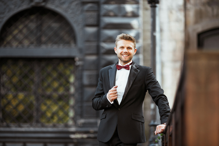 Foto de Wedding photo shooting. Bridegroom standing outdoor and smiling. Man wearing white shirt, black jacket and bow-knot. Waist up, looking at camera - Imagen libre de derechos