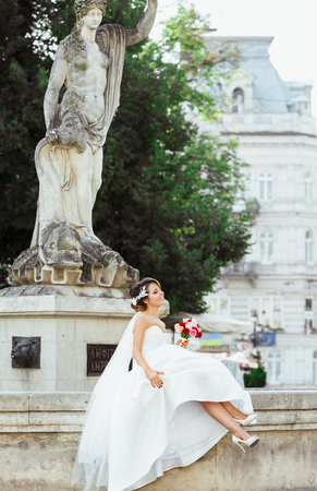 Foto de Wedding photo shooting. Bride sitting near monument in the city. Holding bouquet and smiling. Wearing white dress, white shoes and veil. Outdoor, full body, profile - Imagen libre de derechos