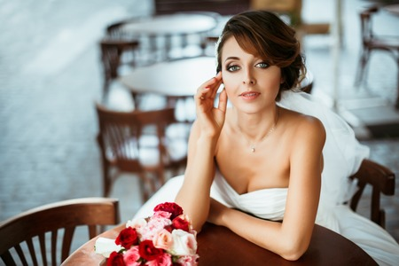 Foto de Wedding photo shooting. Bride sitting in cafe. Hand near face. Bouquet lying on table near her. Wearing white dress. Outdoor, waist up, closeup - Imagen libre de derechos