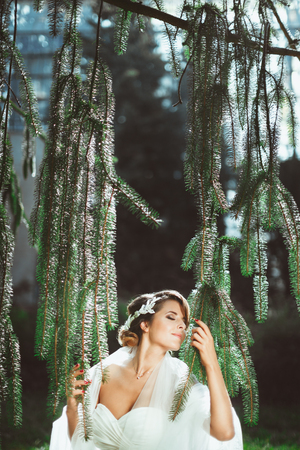 Foto de Bride standing under pine tree. Holding branches with both hands, head turned aside with closed eyes and smiling. Wearing white dress and veil on shoulders. Outdoor, waist up, profile - Imagen libre de derechos