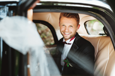 Foto de Wedding day. Bridegroom sitting in wedding car, looking at camera and smiling. Decorations. Sunny day. Waist up, closeup - Imagen libre de derechos