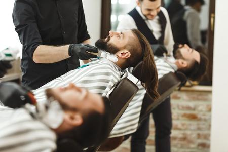 Photo pour Barbers making a beard form for clients - image libre de droit