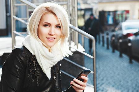 Photo pour Cute girl holding mobile phone and smiling - image libre de droit