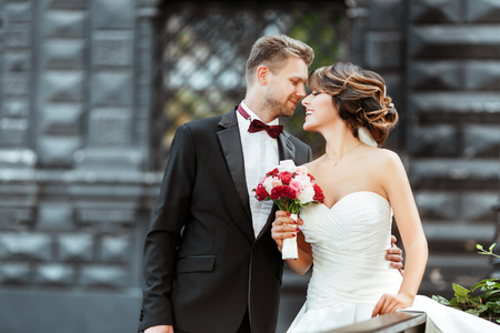 Photo for Bride and bridegroom standing with bouquet and smiling - Royalty Free Image