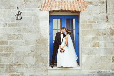 Foto de Bride and bridegroom standing near blue door - Imagen libre de derechos