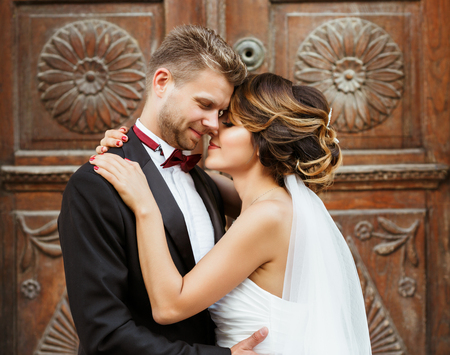 Foto de Bridegroom and bride embracing near wooden door - Imagen libre de derechos