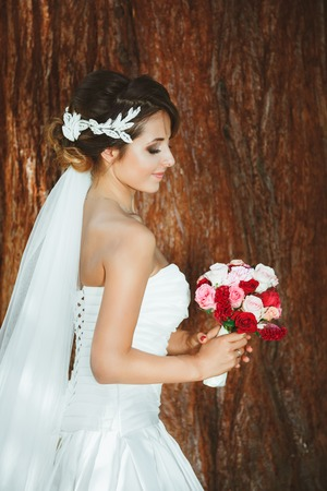 Foto de Bride with closed eyes standing in pine forest - Imagen libre de derechos