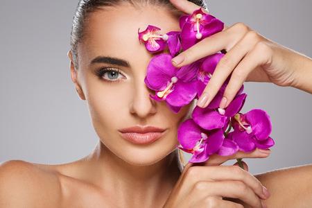 Foto für Girl with orchid closing one eye - Lizenzfreies Bild
