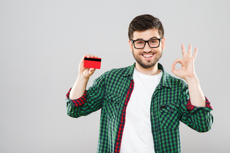 Photo pour Man holding red credit card and showing ok - image libre de droit