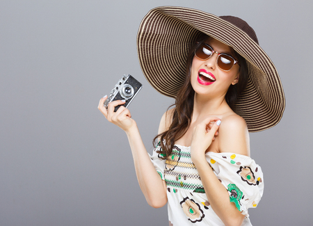 Photo for Model in hat and sunglasses holding camera - Royalty Free Image