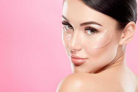 Photo pour Perfect girl with nude make up and naked shoulders at studio background, invisible eye patches on face, skin care concept, looking at camera. - image libre de droit