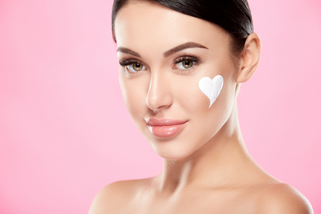 Photo pour Girl with nude make up at studio with face cream - image libre de droit